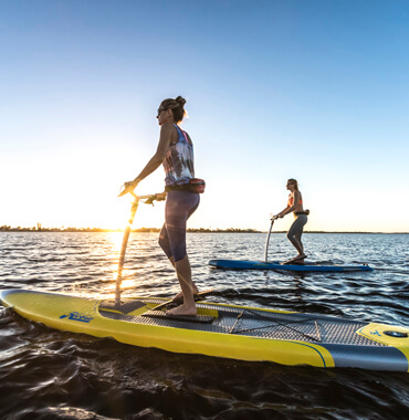 Ladies riding on a Hobie Eclipse boards.