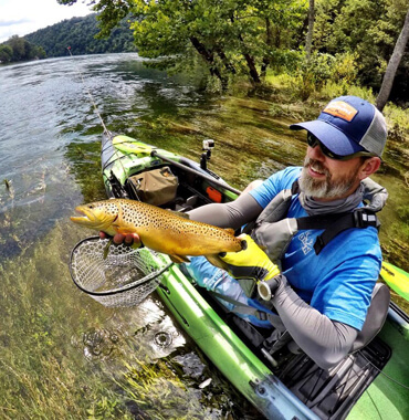 Man holding a brown trout over the side of a Jackson Kayak.